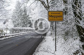 Ein Ortseingangsschild von Meppen an der Straße bei Schnee